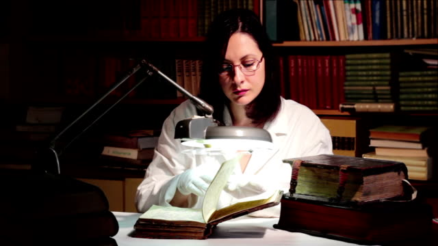 Researching the Old Church Book Scientist studies the old Christian book using the large desktop magnifier, 4 K Video Clip old testament stock videos & royalty-free footage