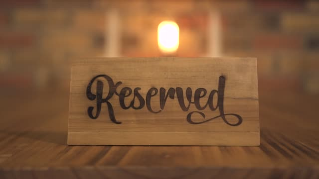 reserved table sign for reservation seat at evening restaurant for candle dinner. reserved table wooden tag in luxury restaurant or cafe for romantic date and dinner with candles - fare una prenotazione video stock e b–roll