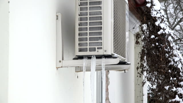 Residential air conditioner unit on frozen with ice on house wall. Zoom out. video