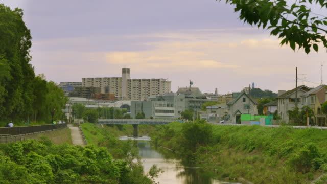 横浜郊外の住宅街と夕暮れ時の鶴見川 - 川岸点の映像素材/bロール