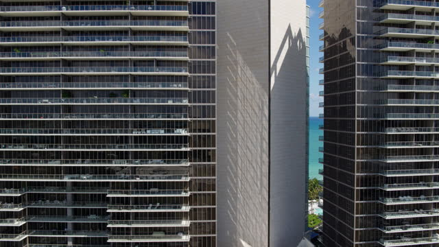 Residential condominiums facades in Bal Harbour, Miami.  Drone-made footage with panning camera motion. Aerial view of Bal Harbour and Surfside, Miami, Florida. 4K UHD B-Roll footage. ocean front properties stock videos & royalty-free footage
