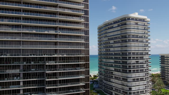 Residential condominiums facades in Bal Harbour, Miami.  Drone-made footage with panning-backward  camera motion. Aerial view of Bal Harbour and Surfside, Miami, Florida. 4K UHD B-Roll footage. ocean front properties stock videos & royalty-free footage