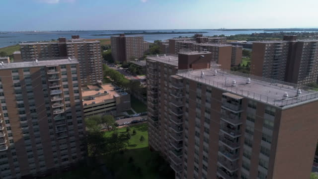 """residential district with multi-level social """"projects"""" brick buildings in brooklyn, new york, along pennsylvania avenue, with shirley chisholm state park and jamaica bay in the backdrop. aerial drone video with the panoramic-forward camera motion. - osiedle mieszkaniowe filmów i materiałów b-roll"""