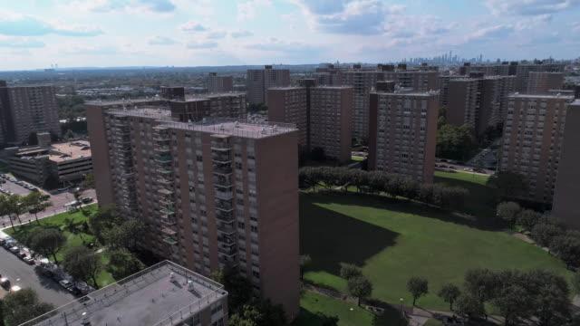 vidéos et rushes de quartier résidentiel avec des bâtiments sociaux à plusieurs niveaux de briques à brooklyn, new york, le long de pennsylvania avenue, avec la vue à distance de manhattan. vidéo de drone aérien avec le mouvement avant de caméra. - hlm