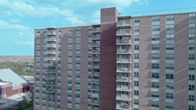 vidéos et rushes de quartier résidentiel avec des bâtiments sociaux à plusieurs niveaux en briques à brooklyn, new york, le long de pennsylvania avenue, avec shirley chisholm state park et jamaica bay en toile de fond. vidéo de drone aérien avec le mouvement ascendant d - hlm