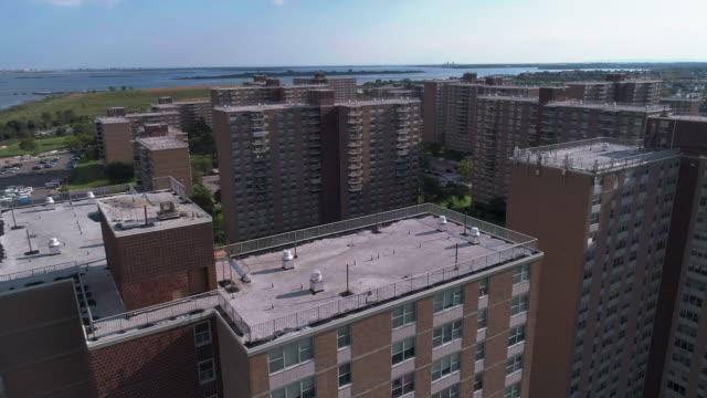 """residential district with multi-level social """"projects"""" brick buildings in brooklyn, new york, along pennsylvania avenue, with shirley chisholm state park and jamaica bay in the backdrop. aerial drone video with the forward camera motion. - osiedle mieszkaniowe filmów i materiałów b-roll"""