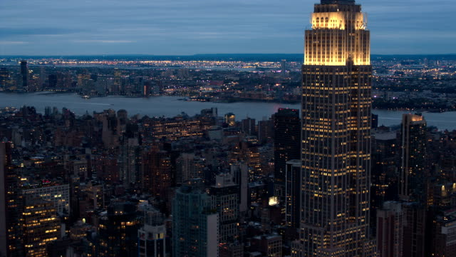 AERIAL: Residential tower blocks near the Hudson River and New Jersy city lights behind the iconic Empire State Building shinning bright at night video