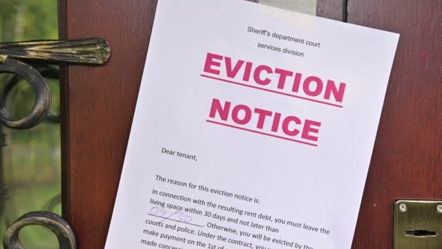 vídeos y material grabado en eventos de stock de aviso de desalojo del residente se pega a la puerta principal de la casa, de cerca - echar