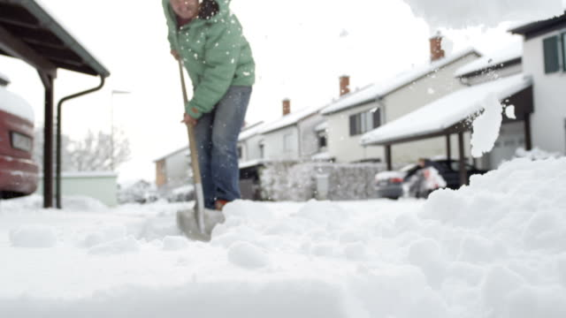 CLOSE UP: Residents shoveling fresh winter snow from the sidewalk and frontyards video