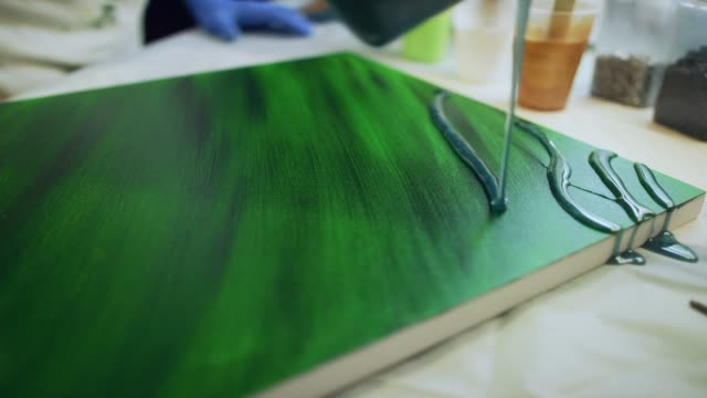 A Resinista / Artist with Safety Gloves Pours Green Epoxy/Resin over a Painted Canvas in an Indoor Art Studio
