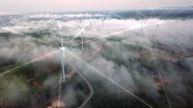 4K Resolution Aerial view of connection technology with Wind Turbine field on fog and mist over landscape,wind power and Alternative Energy concept