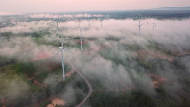 4k resolution aerial view of wind turbine field on fog and mist over landscape,eolic park,wind power and alternative energy concept - turbina a vento video stock e b–roll