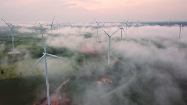 vídeos de stock e filmes b-roll de 4k resolution aerial view of wind turbine field on fog over landscape,eolic park,wind power and alternative energy concept - origens