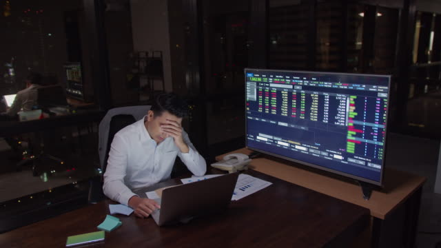 4K resolution Asian Business man working late and thinking with serious action on the table in front of computer laptop at office in the dark,Business Financial and investment concept.Work late and Work hard concept.Business man worried about his business