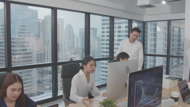 4K resolution Asian manager or boss teaching and explaining work in office.business partners discussing and brainstorming plan.Investment financial analysis concept,Asian Business indoors life style.Asian colleague and teamwork concept,