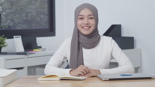 4k resolution beautiful asian muslim woman talking to camera,attractive asian muslim woman smiling video conference,modern muslim woman from the south east and east asian region lifestyle concept - etnia malese video stock e b–roll