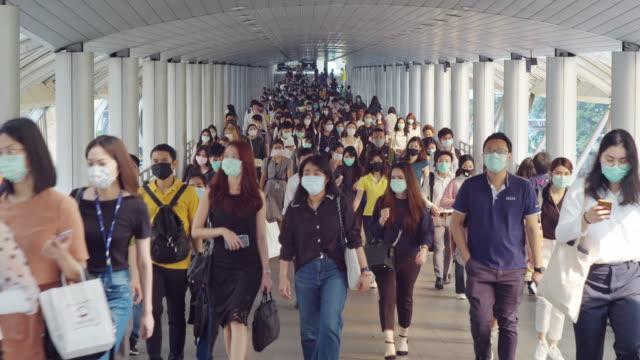 朝のラッシュアワーにバンコクの職場に行く間、コロナウイルスまたはcovid-19とマイクロダストpm 2.5の予防で顔保護を身に着けているアジアの人々の4k解像度の群衆 - マスク点の映像素材/bロール