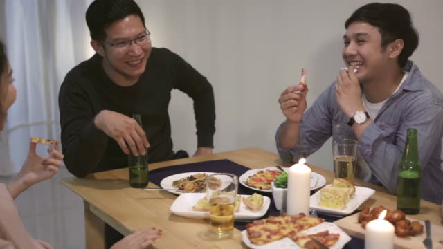 4K Resolution Group of Asian friends having fun talk in Christmas Dinner Party.Happy Thai people having fun together eating pizza during party at home.