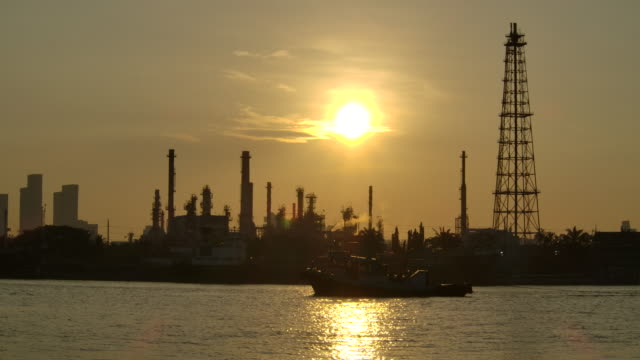 4K Resolution Oil refinery In the morning at sunrise with reflection silhouette structure of the chimney of Flue gas release