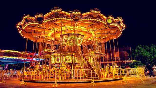 vídeos de stock, filmes e b-roll de lapso de tempo de resolução 4k, cinemagraph longa exposição. carrossel de casa voadora está jogando a iluminação para girar uma volta e parar durante a noite, celebrar e filtro de fundo carnaval engraçado com vintage. - moda parisiense