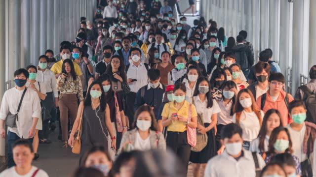 4k upplösning tid förfaller folkmassor av asiatiska människor bär ansikte skydd i förebyggande för coronavirus eller covid-19 och mikro damm pm 2,5 i luften samtidigt som de går till sin arbetsplats i bangkok på morgon rusningstid - cold street bildbanksvideor och videomaterial från bakom kulisserna
