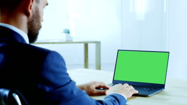 Respectable Businessman Working on the Laptop with Isolated Mock-up Green Screen. His Office is Bright and Modern. Respectable Businessman Working on the Laptop with Isolated Mock-up Green Screen. His Office is Bright and Modern. Shot on RED EPIC-W 8K Helium Cinema Camera. business laptop stock videos & royalty-free footage