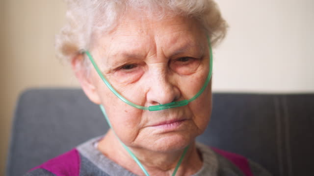 Respiratory oxygen nasal catheter to senior woman Respiratory oxygen nasal catheter to senior woman medical oxygen equipment stock videos & royalty-free footage