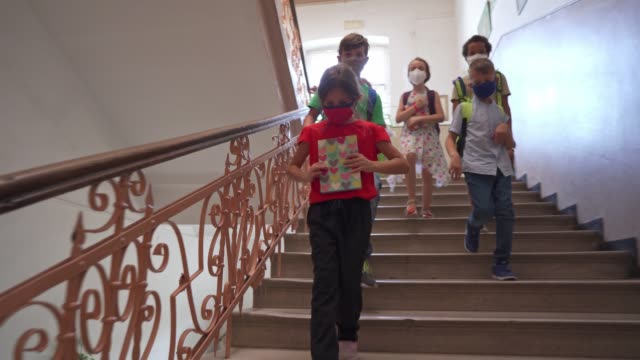 responsible group of multiracial elementary school kids going down the stairs for their class while wearing protective face mask and keeping social distancing - didattica a distanza video stock e b–roll