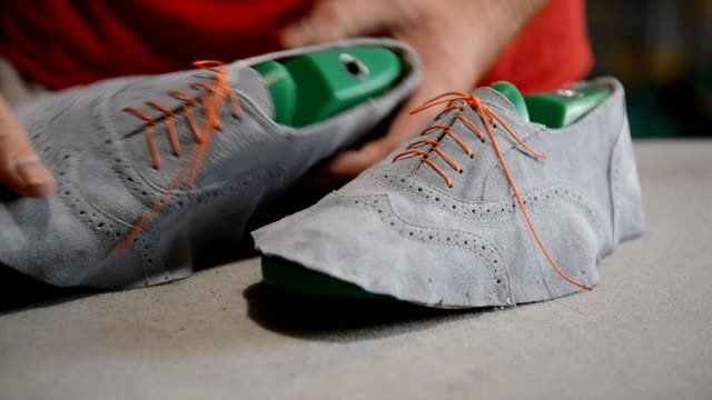 Responsible shoemaker making gray shoes video