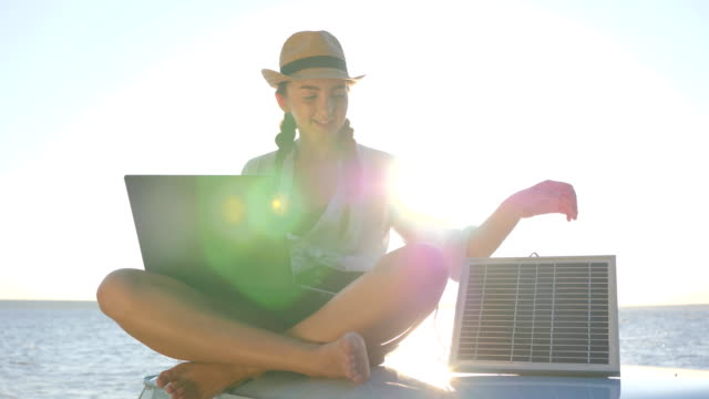 rest, fun girl sits on roof retro car with solar battery and laptop in hands outdoors, young woman sitting on car roof video