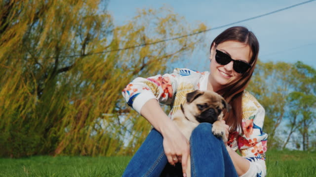 Rest in the park with a dog and snack on the go hot dog. A young woman sits on the lake in a park playing with her pug video