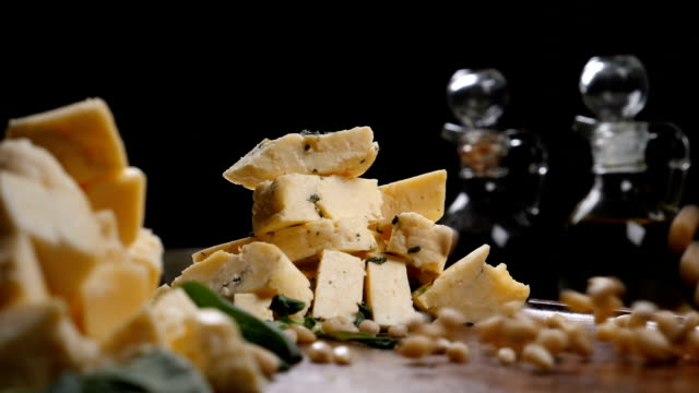 Restaurant art concept. Different sorts of cheese put in heaps on wooden background. Handful of pine nuts in slow motion Restaurant art concept. Different sorts of cheese put in heaps on wooden background. Handful of pine nuts in slow motion. Hd pine nut stock videos & royalty-free footage