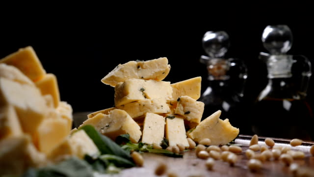 Restaurant art concept. Different sorts of cheese put in heaps on black background. Handful of pine nuts in slow motion Restaurant art concept. Different sorts of cheese put in heaps on black background. Handful of pine nuts in slow motion. Hd pine nut stock videos & royalty-free footage