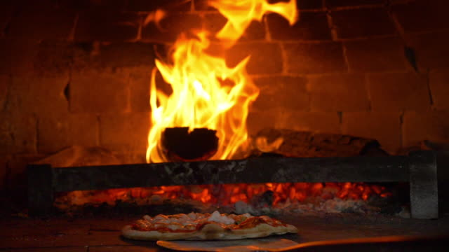 Restaurant chef Italian pizza is cooked takes pizza  in a wood fired oven at traditional restaurant.Close up pizza in firewood oven with flame behind being pulled from mobile wood fired oven