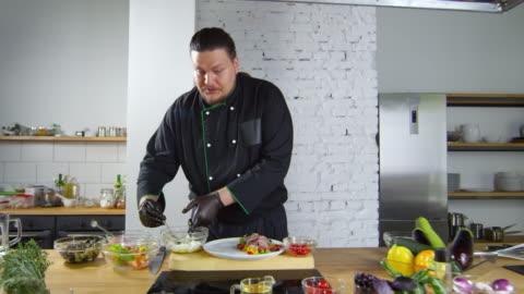 vídeos de stock e filmes b-roll de restaurant chef showing how to plate salad - mostrar