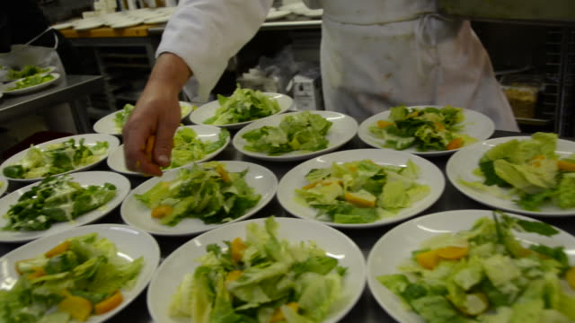 restaurant kitchen chef sprinkles croutons on caesar salads video
