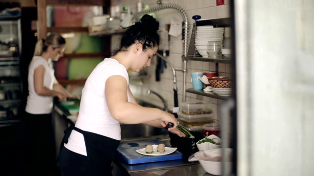 Restaurant kitchen woman preparing fish dishes for guests video