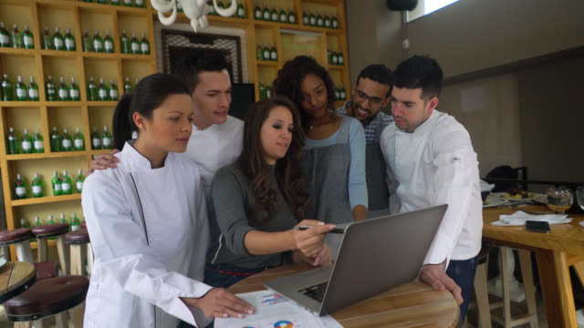 Restaurant manager explaining to her team something while pointing at laptop video