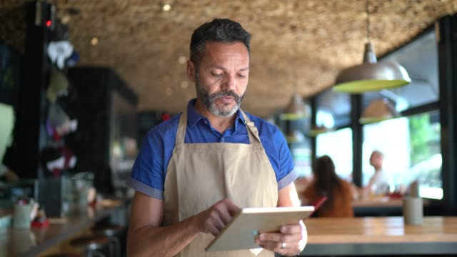 Restaurant manager using tablet portrait Restaurant manager using tablet portrait wait staff stock videos & royalty-free footage