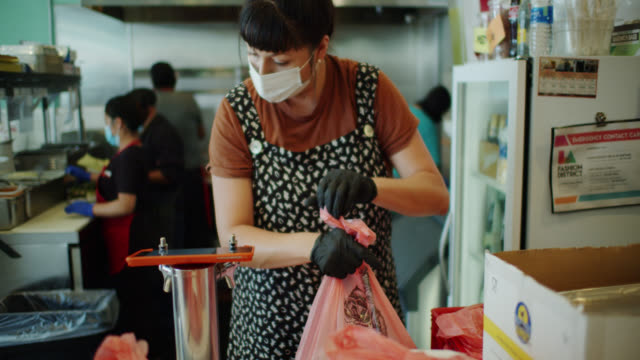 Restaurant Staff Wearing Masks and Gloves at Work During Covid-19 Lockdown Assembling Orders for Pick-up and Delivery