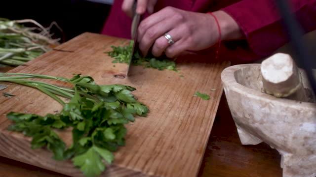Restaurant worker chopping fresh cilantro and parsley - stabilized shot