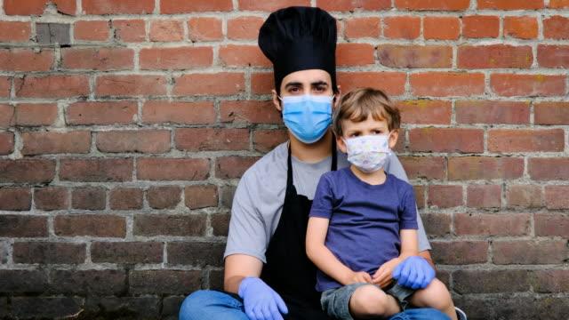 restaurant worker posing with his son, both wearing protective masks - mestiere nella ristorazione video stock e b–roll