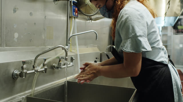 vídeos de stock e filmes b-roll de restaurant worker washing hands in large sink during covid-19 outbreak - servir comida e bebida