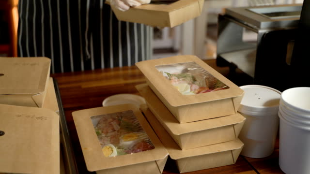 restaurant worker wearing medical mask and gloves collecting a food box take away. - mestiere nella ristorazione video stock e b–roll