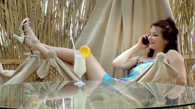 Resting girl in hammock talks on phone video