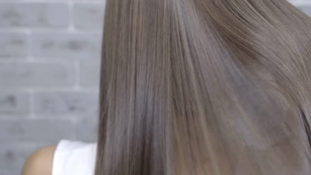 result after lamination and hair straightening in a beauty salon for a girl with brown hair. hair care concept - гладкая поверхность стоковые видео и кадры b-roll