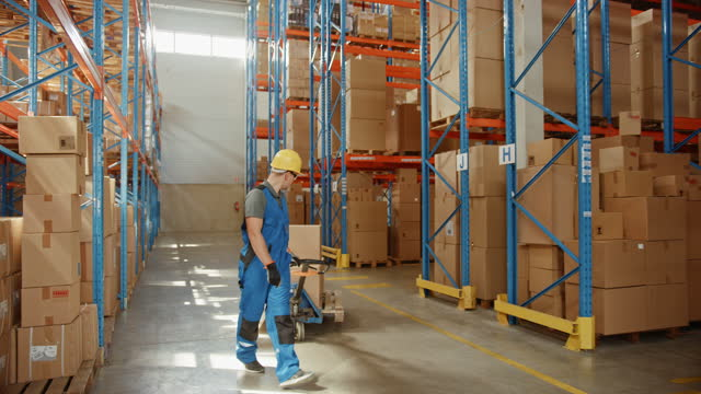 Retail Delivery Warehouse full of Shelves with Goods in Cardboard Boxes, Workers Scan and Sort Packages, Move Inventory with Pallet Trucks and Forklifts. Product Distribution Logistics Center. Dolly