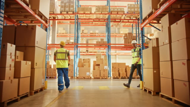 Retail Warehouse full of Shelves with Goods in Cardboard Boxes, Workers Scan and Sort Packages, Move Inventory with Pallet Trucks and Forklifts. Product Distribution Logistics Center. Dolly Shot