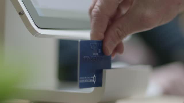 ecu slo mo. 小売労働者は、現代のショップのチェックアウトカウンターで顧客のためにクレジットカードとスピンタブレットをスワイプします。 - クレジット決済点の映像素材/bロール