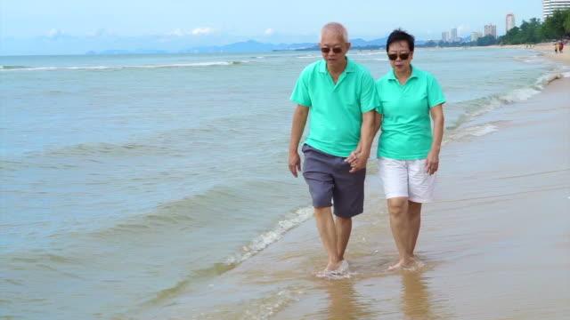 retired asian senior couple walking on tropical beach morning with beautiful sky - cultura coreana video stock e b–roll
